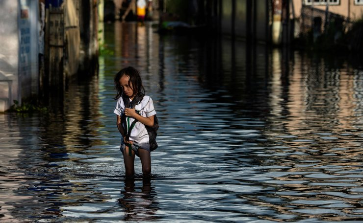 This photo taken on October 8, 2018 shows an elementary student wading through floodwaters in Mabalacat, Pampanga. - Areas north of Manila like the provinces of Pampanga and Bulacan have sunk four-six centimetres (1.5-2.4 inches) a year since 2003, according to satellite monitoring. The creeping bay waters put people and property at risk, while the threat is amplified by high-tides and flooding brought by the roughly 20 storms that pound the archipelago every year. AFP