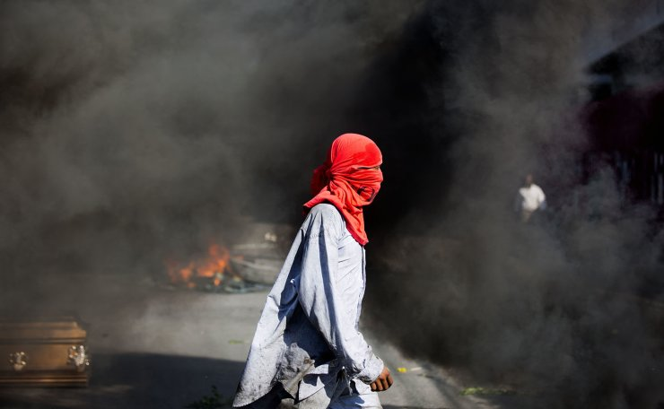 A masked demonstrator walks past a coffin containing the body of a protester who was killed during the week's previous protests in Port-au-Prince, Haiti, Monday, March 4, 2019. Protesters are angry about skyrocketing inflation and the government's failure to prosecute embezzlement from a multi-billion Venezuelan program that sent discounted oil to Haiti. AP