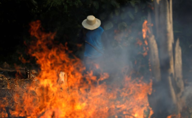 A man works in a burning tract of Amazon jungle as it is being cleared by loggers and farmers in Iranduba, Amazonas state, Brazil August 20, 2019. Reuters