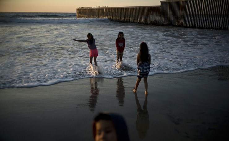 Children play at the beach near the border fence in Tijuana, Mexico, Sunday, Nov. 18, 2018. While many in Tijuana are sympathetic to the plight of Central American migrants and trying to assist, some locals have shouted insults, hurled rocks and even thrown punches at the migrants. AP