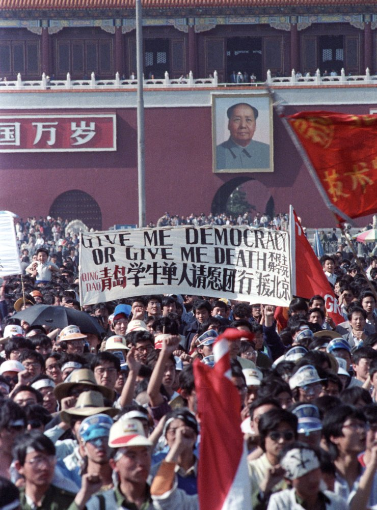 Chinese students carry a sign that reads, 'Give me democracy or give me death,' during a demonstration in Tiananmen Square in Beijing, China, May 14, 1989. The entrance to the Forbidden City with a portrait of the late Chairman Mao is in the background. Reuters