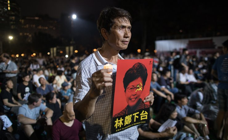 A participant holds a photo of Hong Kong Chief Executive Carrie Lam with the words 'step down' on it during the annual candlelit vigil commemorating the 30th anniversary of the 1989 Beijing Tiananmen Square massacre at Victoria Park in Hong Kong, China, 04 June 2019. EPA