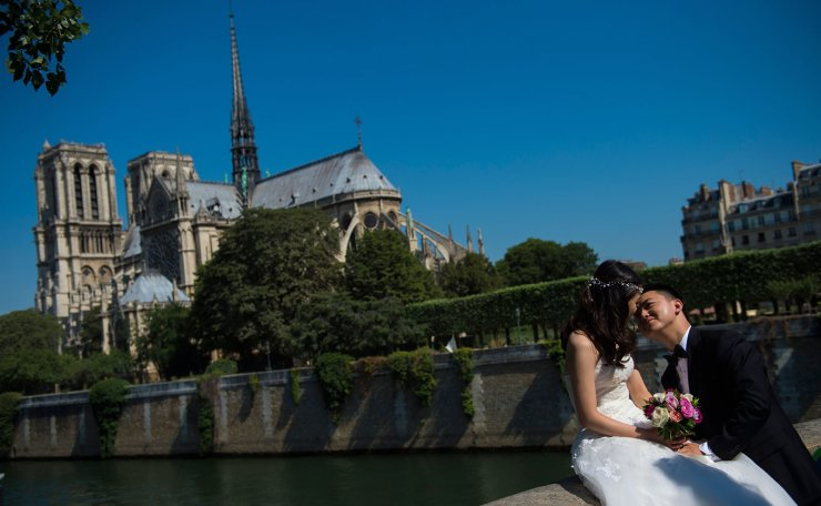 In this file photo taken on July 16, 2015 a couple pose for wedding pictures in front of Notre-Dame de Paris Cathedral in Paris. AFP