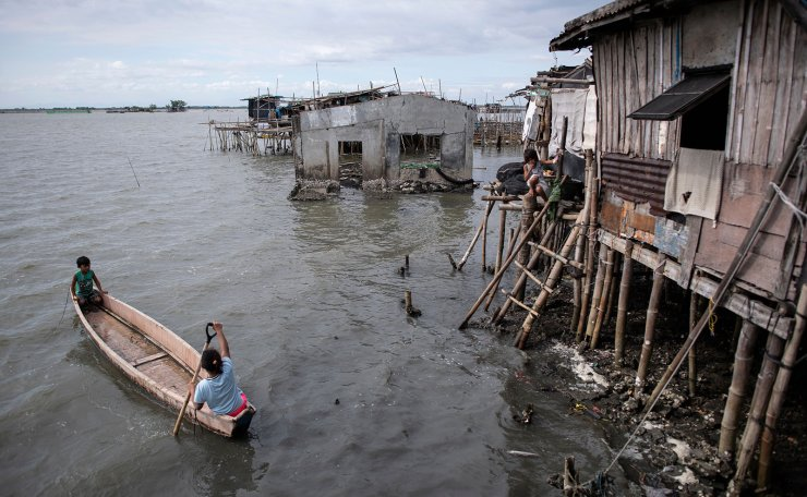This photo taken on February 3, 2019 shows residents using a boat to travel across the water in Sitio Pariahan, Bulacan. - Areas north of Manila like the provinces of Pampanga and Bulacan have sunk four-six centimetres (1.5-2.4 inches) a year since 2003, according to satellite monitoring. AFP
