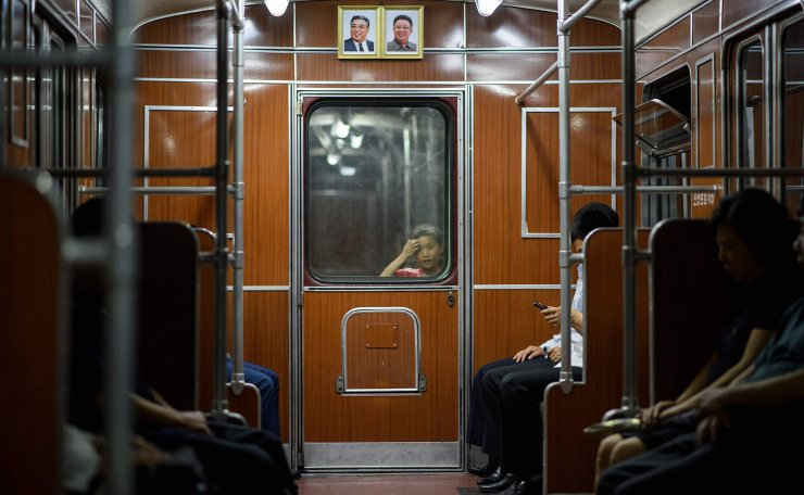 A child looks through a window separating subway train carriages beneath the portraits of late North Korean leaders Kim Il Sung and Kim Jong Il in Pyongyang on June 17, 2019. AFP