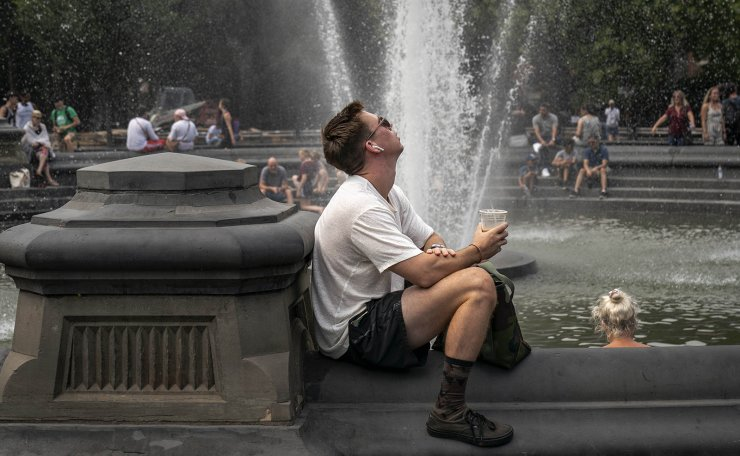 People cool off near the fountain at Washington Square Park during a hot afternoon day on July 17, 2019 in New York City. Sweltering heat is moving into the New York City area, with temperatures expected to rise close to 100 degrees by this weekend. The large heat wave will affect close to two thirds of the United States, with the East Coast and Midwest seeing the worst conditions. AFP