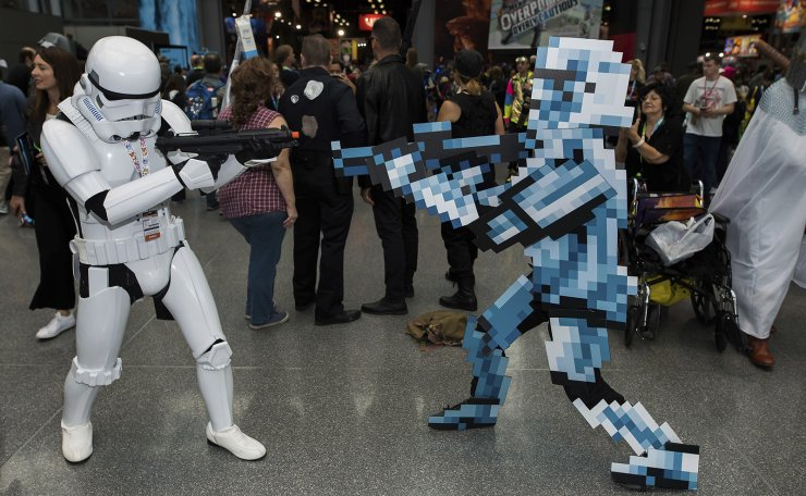 Attendees dressed as a Star Wars stormtrooper and pixelated video game stormtrooper pose during New York Comic Con at the Jacob K. Javits Convention Center on Sunday, Oct. 6, 2019, in New York. The costume at right is made of cardboard. AP