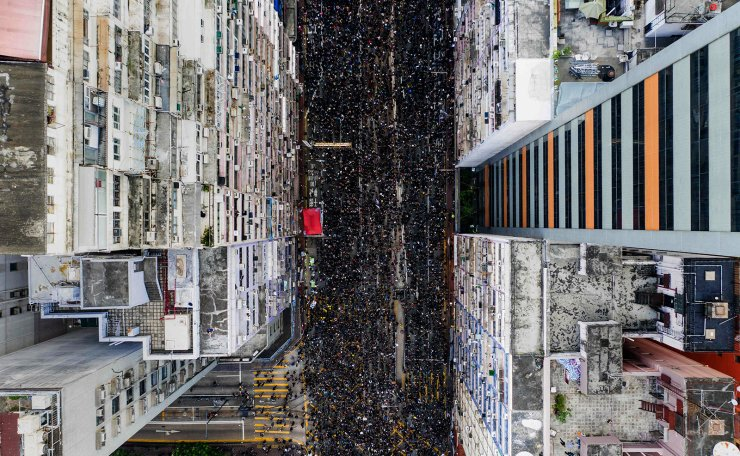 This overhead view shows thousands of protesters marching through the street as they take part in a new rally against a controversial extradition law proposal in Hong Kong on June 16, 2019. AFP