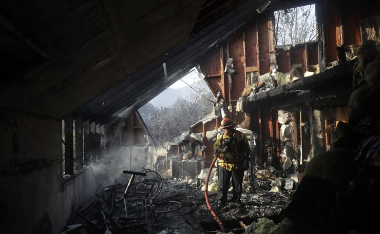 Capt. Adrian Murrieta with the Los Angeles County Fire Dept., looks for hot spots on a wildfire-ravaged home Saturday, Nov. 10, 2018, in Malibu, Calif. AP