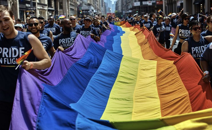 FILE- In this June 24, 2018 file photo, revelers carry a Rainbow Flag along Fifth Avenue during the New York City Pride Parade in New York. June 28, 2019 marks the 50th anniversary of the Stonewall uprising, which fueled the fire for a global LGBTQ movement. From symposiums to movie screenings, walking tours to art exhibits, even an opera, a slew of institutions and organizations are filling June with events that commemorate that moment and its impact through the last five decades. AP