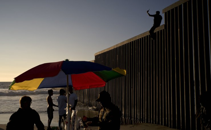A Mexican citizen climbs the border fence to take pictures of himself, in Tijuana, Mexico, Sunday, Nov. 18, 2018.  AP