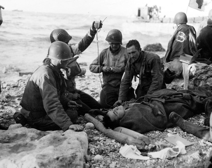 FILE - In this June 1944, file photo, U.S. Army medical personnel administer a transfusion to a wounded comrade, who survived when his landing craft went down off the coast of Normandy, France, in the early days of the Allied landing operations. AP
