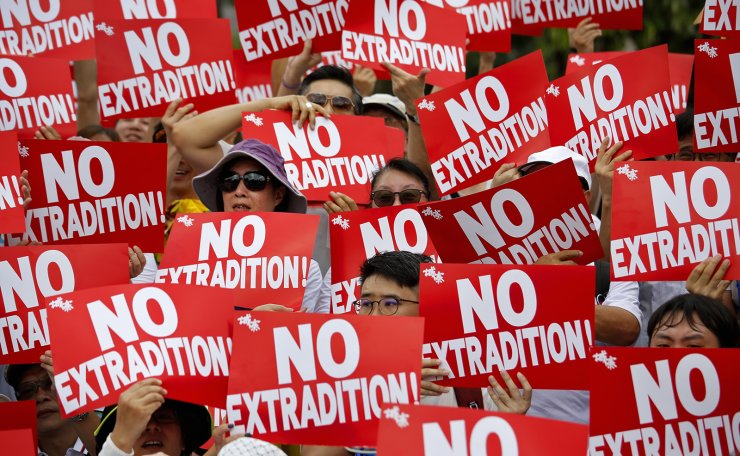 Protesters hold placards as they stage protest against the extradition law in Hong Kong, Sunday, June 9, 2019. AP