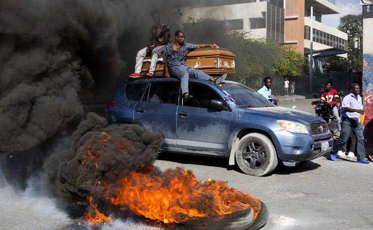 A car carries a coffin containing the body of one of the demonstrators who was killed during previous protests in Port-au-Prince, Haiti, Monday, March 4, 2019. AP