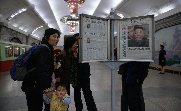 Commuters look at a copy of the Rodong Sinmun newspaper showing an image of North Korea's leader Kim Jong Un, at a newstand in a subway station in Pyongyang on April 13, 2019. AFP