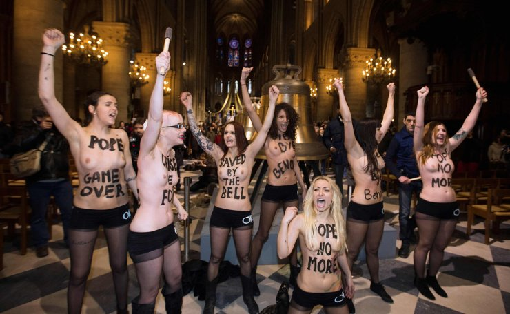 In this file photo taken on February 12, 2013 activists from the women's rights organisation Femen protest in front of the new eight bronze bells displayed in the nave of Notre-Dame de Paris Cathedral in Paris. AFP