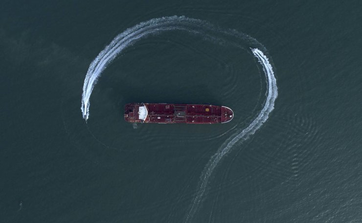 In this Sunday, July 21, 2019 photo, an aerial view shows a speedboat of Iran's Revolutionary Guard moving around the British-flagged oil tanker Stena Impero which was seized in the Strait of Hormuz on Friday by the Guard, in the Iranian port of Bandar Abbas. Global stock markets were subdued Monday while the price of oil climbed as tensions in the Persian Gulf escalated after Iran's seizure of a British oil tanker on Friday. AP