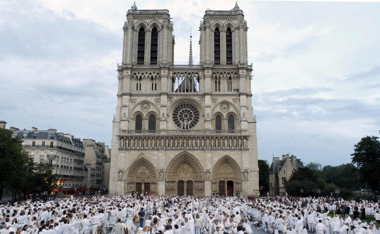 In this file photo taken on June 14, 2012 people, all dressed up in white, stand prior to a dinner in a US-style flash mob-event in front of the Notre-Dame de Paris Cathedral in central Paris. AFP