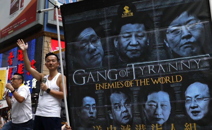 Protesters display a banner as protesters march along a downtown street to against the proposed amendments to an extradition law in Hong Kong Sunday, June 9, 2019. AP
