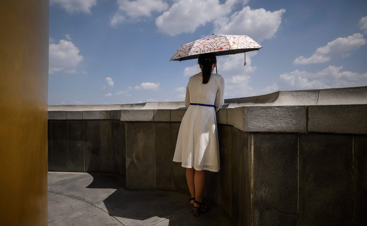 <span>In a photo taken on June 16, 2019 a North Korean tour guide holding an umbrell a looks out from a viewing platform of the Juche tower overlooking the city skyline of Pyongyang. AFP</span><br /><br />