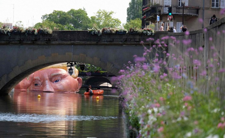 A picture taken on July 5, 2019 shows the installation 'Everything is fine' depicting the half submerged head of US President Donald Trump by Jacques Rival, architect, displayed in the Moselle river as part of the digital art festival 'Constellations de Metz' in Metz, eastern France. AFP