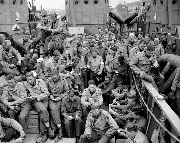 FILE - In this June 5, 1944, file photo, U.S. serviceman attend a Protestant service aboard a landing craft before the D-Day invasion on the coast of France. AP