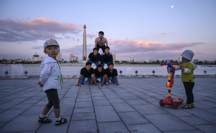 <span>In a photo taken on June 15, 2019 children watch as a group of Korean visitors from Japan perform a gymnastic routine on banks of the Taedong river before the landmark Juche tower in Pyongyang. AFP</span><br /><br />