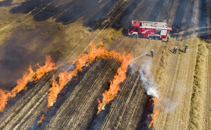 A picture taken with a drone shows firefighters extinguishing a burning field near Nagykanizsa, Hungary, 21 July 2019, after a farm machine caught fire and caused stubble burning. EPA