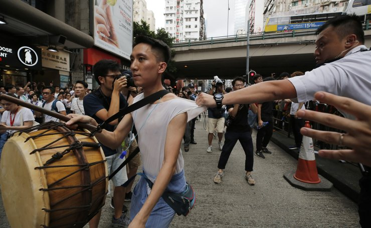 A protester is grabbed by a policeman as he crosses the police line during a rally against the proposed amendments to the extradition law in Hong Kong, Sunday, June 9, 2019. AP