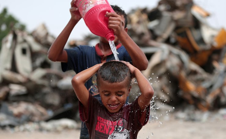 A Palestinian child is poured with water to stay cool during hot weather, in the southern Gaza Strip city of Khan Younis, July 17, 2019. Xinhua