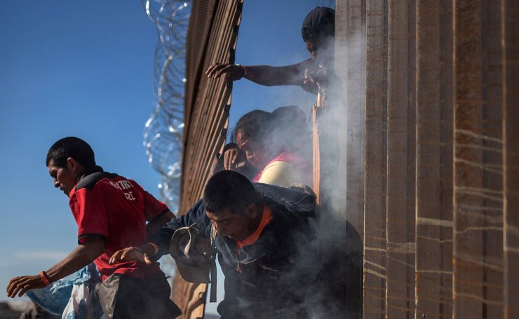 Migrants, part of a caravan of thousands from Central America trying to reach the United States, return to Mexico after being hit by tear gas by U.S. Customs and Border Protection (CBP) after attempting to illegally cross the border wall into the United States in Tijuana, Mexico November 25, 2018. Reuters