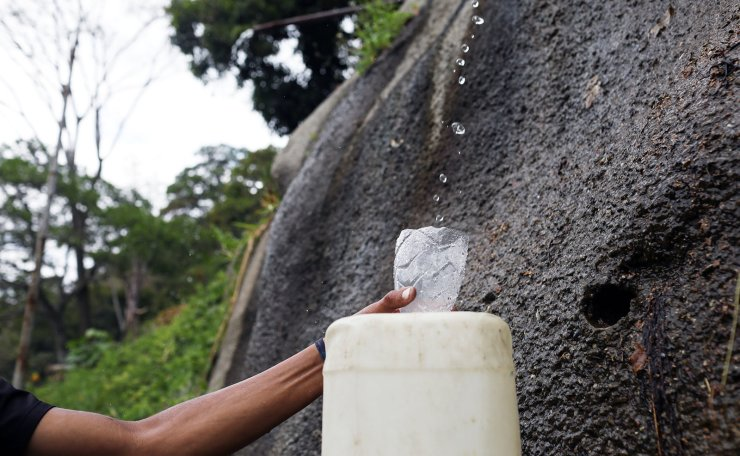 A man fills a tank with water coming from the mountain in Caracas, Venezuela March 11, 2019. Reuters