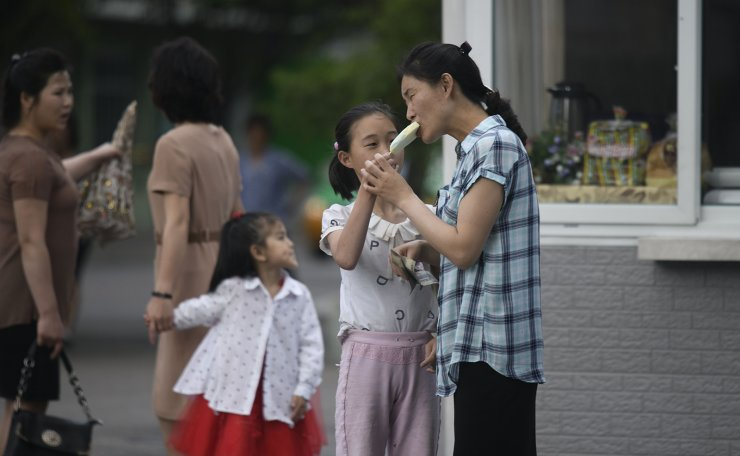<span>In a photo taken on June 16, 2019 a gild holds an ice cream as a woman takes a bite, next to a street-side food stall in Pyongyang. AFP</span><br /><br />