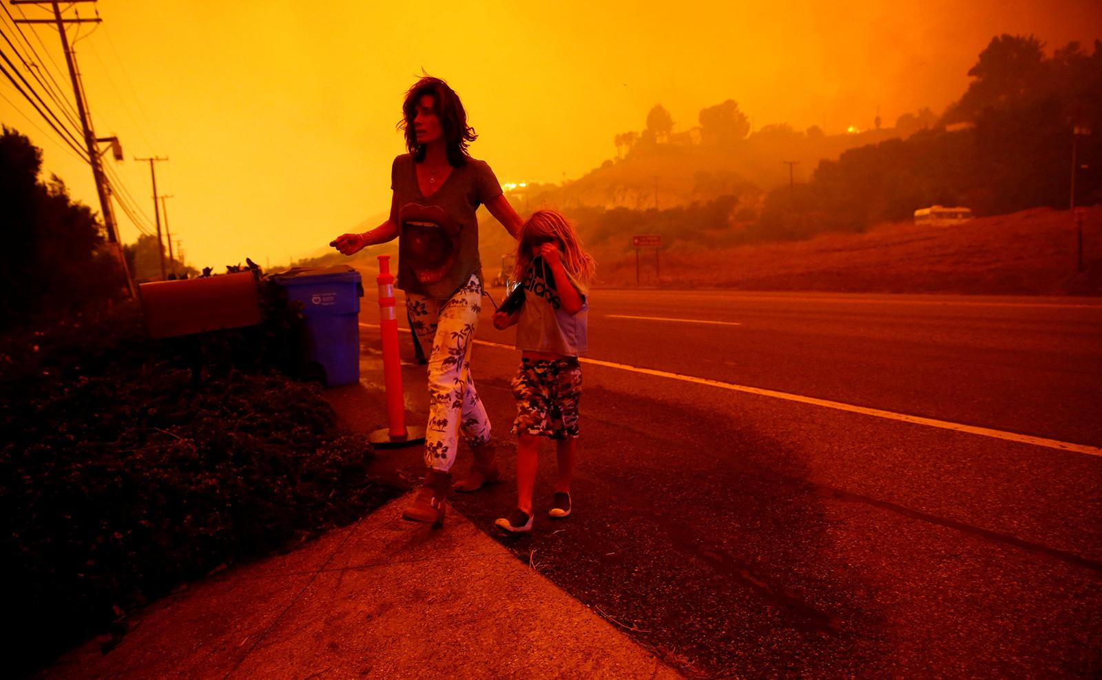 Gabi and Jonah Frank walk on Pacific Coast Highway as the Woolsey Fire threatens their home in Malibu, California, U.S. November 9, 2018. Reuters