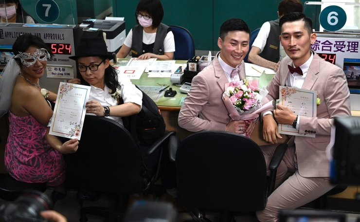 <span>Taiwan's gay couple Shane Lin (2ndR), Marc Yuan and Cynical Chick (L) and Li Ying-Chien display their wedding certificates after registering at the Household Registration Office in Shinyi District in Taipei on May 24, 2019. AFP</span><br /><br />