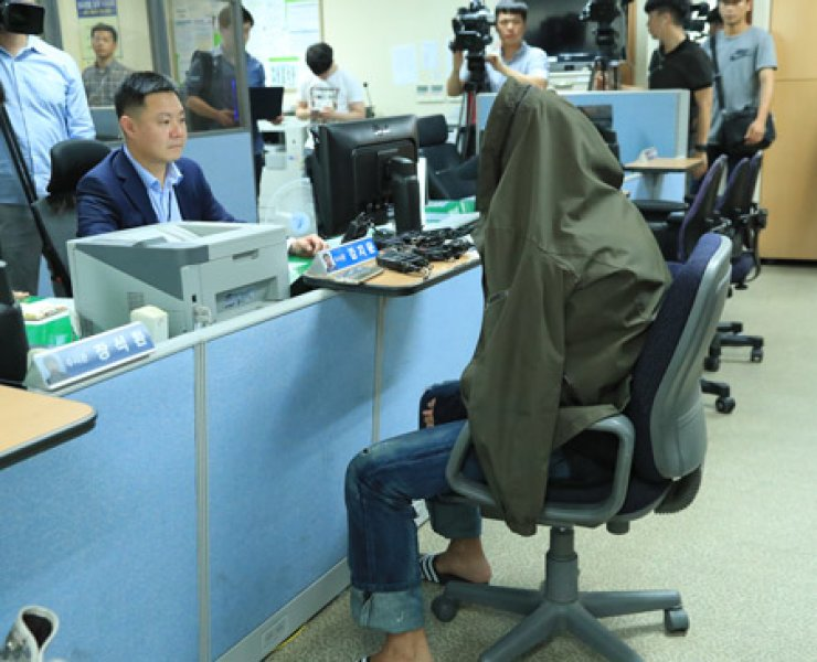 Hiding his face with a jacket, the Grammy-nominated British DJ sits at Seoul Metropolitan Police Agency. / Yonhap