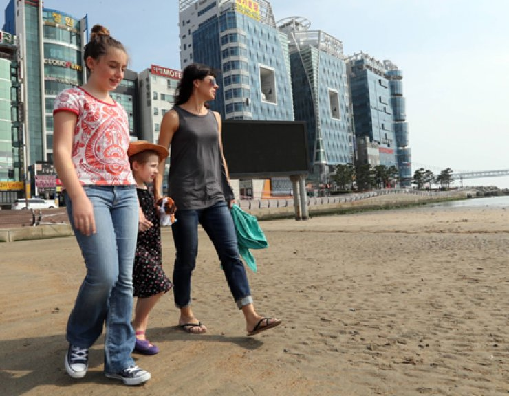 From left: Sisters Fiona and Stella Rupert and their mother Deanna walk on Gwangalli Beach in Busan which they cleaned on Oct. 5 after typhoon Chaba wrecked it. / Yonhap