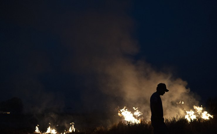 Neri dos Santos Silva, center, is silhouetted against an encroaching fire threat after he spent hours digging trenches to keep the flames from spreading to the farm he works on, in the Nova Santa Helena municipality, in the state of Mato Grosso, Brazil, Friday, Aug. 23, 2019. Under increasing international pressure to contain fires sweeping parts of the Amazon, Brazilian President Jair Bolsonaro on Friday authorized use of the military to battle the massive blazes. AP