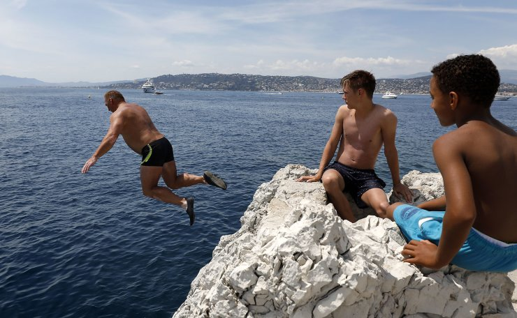 People dive into the Mediterranean Sea on a hot summer's day in Antibes, southern France, 17 July 2019. Temperatures in Antibes reached 29 degrees Celcius. EPA