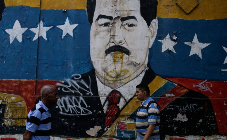 People walk by a graffiti depicting Venezuelan president Nicolas Maduro in Caracas on March 11, 2019. - Venezuela's opposition leader Juan Guaido urged lawmakers Monday to declare a 'state of alarm' to pave the way for the delivery of international aid as the country's devastating blackout entered its fifth day. AFP
