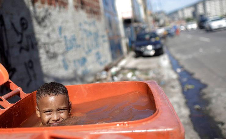 A boy plays inside a trash can used as a water container for a car wash in Rio de Janeiro, Brazil March 19, 2019. Reuters