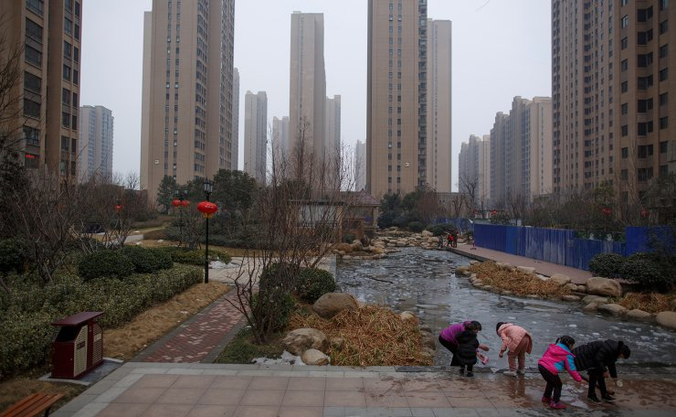 People play with ice floating at a pond in the compound of an apartment complex in Zhengzhou, Henan province, China February 20, 2019. Reuters