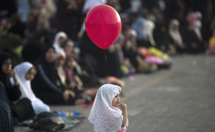 A girl holds a balloon in front of Palestinians performing Eid al-Fitr prayers marking the end of the holy fasting month of Ramadan, in Nuseirat refugee camp, central Gaza Strip, Wednesday, June 5, 2019. AP