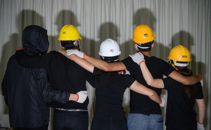 This picture taken on June 14, 2019, shows a group of student protesters posing while wearing their protective clothing during an interview with AFP in Hong Kong, who took part in the protests on June 12, which saw police armed with tear gas and rubber bullets. - Hong Kong's tech-savvy protesters are going digitally dark as they try to avoid surveillance and potential future prosecutions, disabling location tracking on their phones, buying train tickets with cash and purging their social media conversations. AFP