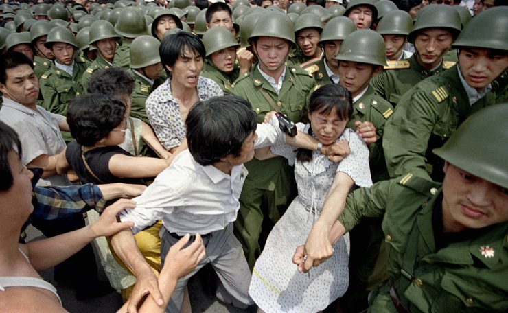 FILE - In this June 3, 1989 file photo, a young woman is caught between civilians and Chinese soldiers, who were trying to remove her from an assembly near the Great Hall of the People in Beijing. AP