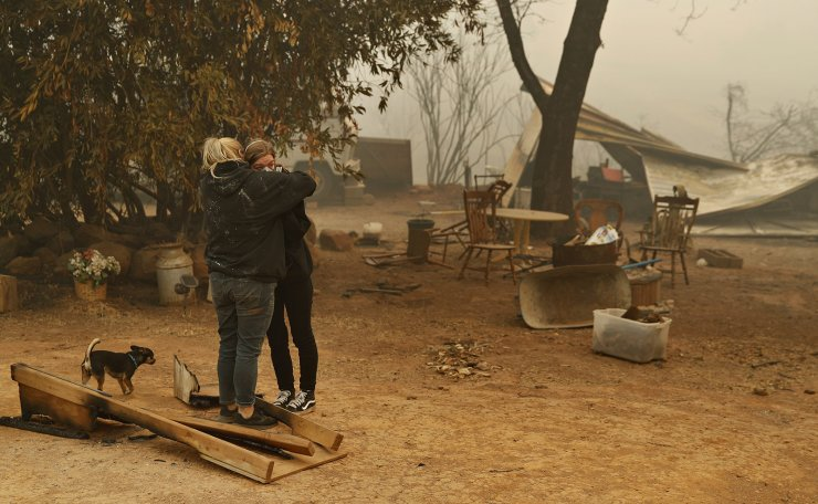 Krystin Harvey, left, comforts her daughter Araya Cipollini at the remains of their home burned in the Camp Fire, Saturday, Nov. 10, 2018, in Paradise, Calif. AP