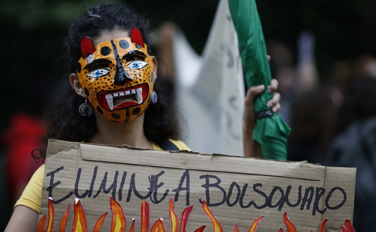 A woman wears an animal mask and carries a sign with a message that reads in Spanish: 'Eliminate Bolsonaro,' during a protest against Brazil's President Jair Bolsonaro and calling for action to protect the Amazon rainforest, outside Brazil's embassy in Mexico City, Friday, Aug. 23, 2019. Under increasing international pressure to contain fires sweeping parts of the Amazon, Bolsonaro on Friday authorized use of the military to battle the massive blazes. AP