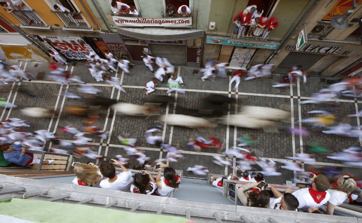 Several 'mozos', or runners, are chased by bulls of Victoriano del Rio ranch during the fifth 'encierro,' or running-with-the-bulls, of the Sanfermines festivities in Pamplona, Spain, 11 July 2019. EPA