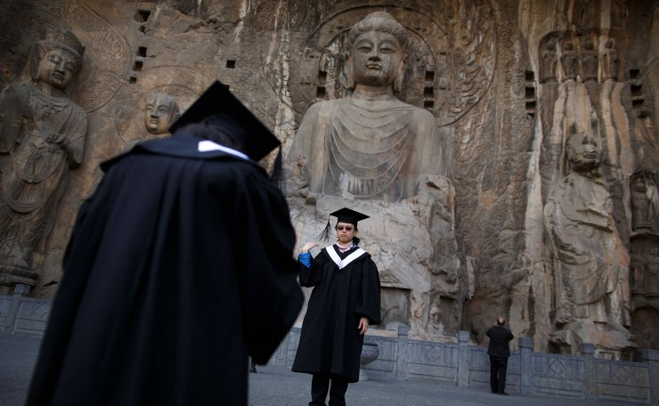 Women in graduation dresses take pictures in front of Buddha statues at the Longmen Grottoes in Luoyang, Henan province, China January 21, 2019. Reuters