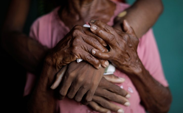The hands of Aidalis Guanipa, 25, a kidney disease patient, and her 83-year-old grandmother, are seen as they pose for a photo, while they wait for the electricity to return, at her house during a blackout, in La Concepcion, Venezuela, April 12, 2019. Reuters
